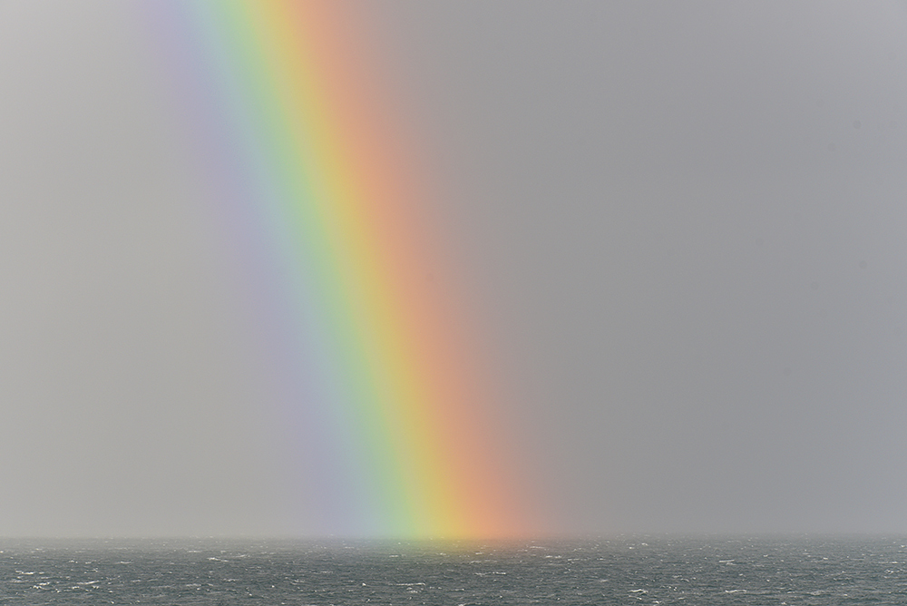 Picture of the bottom of a rainbow above the sea