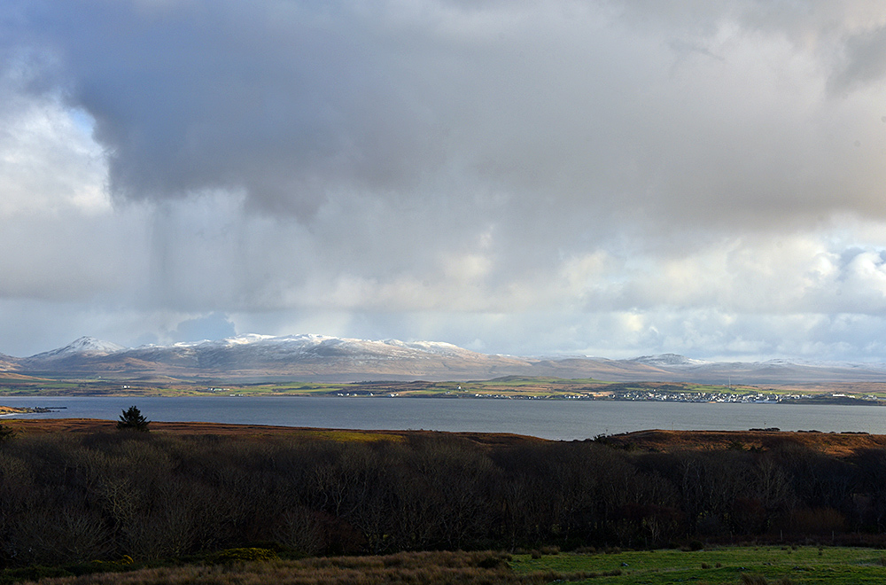 Picture of snow capped hills in the distance seen across a sea loch