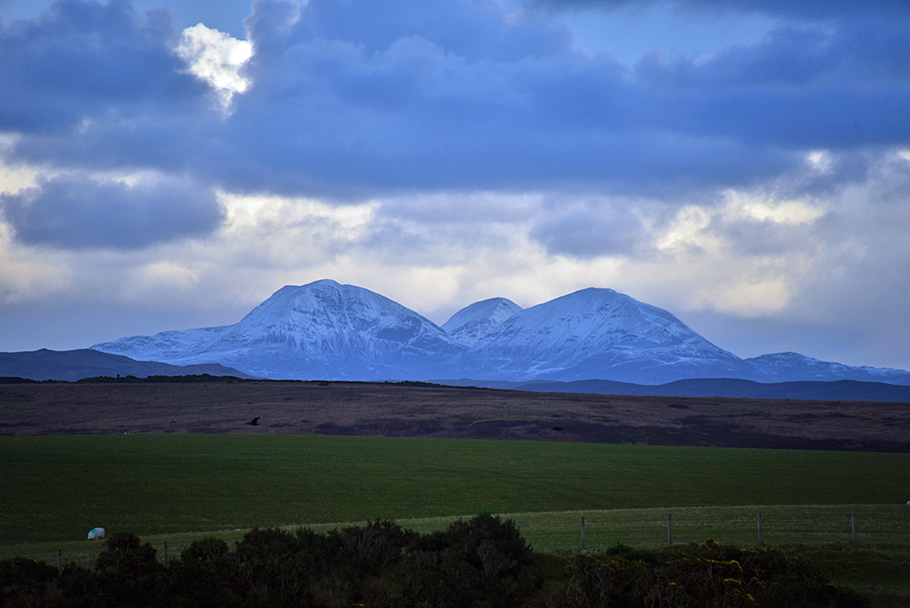 Picture of three snow covered mountains seen across fields