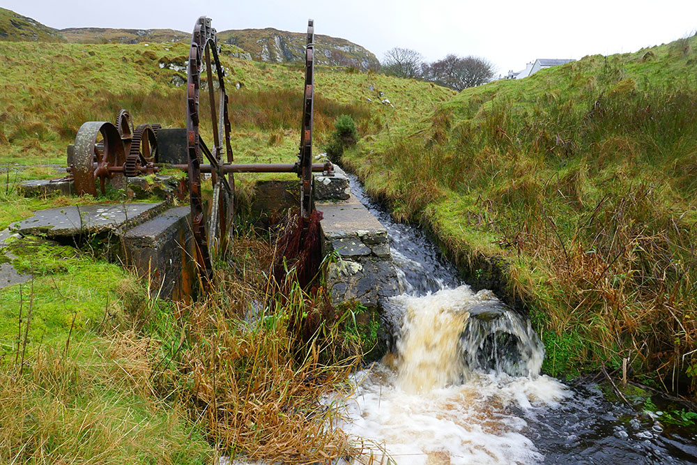 Picture of the remains of an old iron water wheel, the water supply still flowing past it