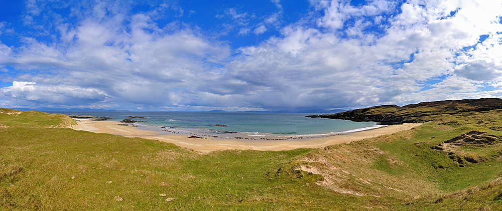 Panoramic picture of a small golden sandy beach in Scotland
