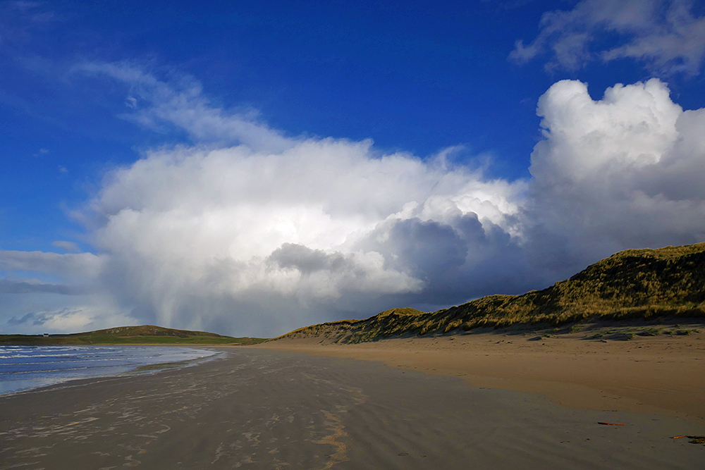 Picture of some dramatic heavy clouds above a line of dunes along a beach