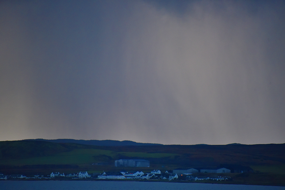 Picture of heavy rain falling behind a coastal village with a distillery