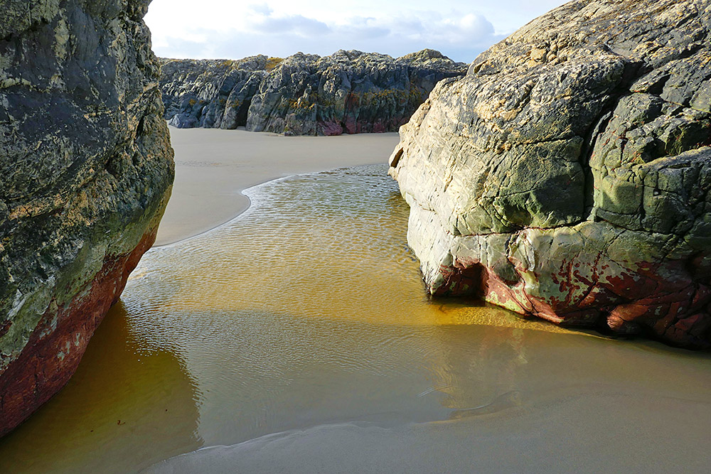 Picture of a beach between two large rocks, illuminated by the November morning sun
