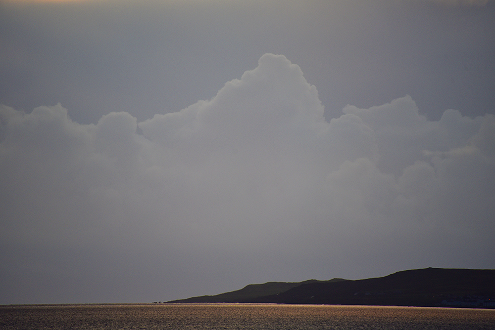 Picture of a cloudy yet bright sky above a sea loch on an island