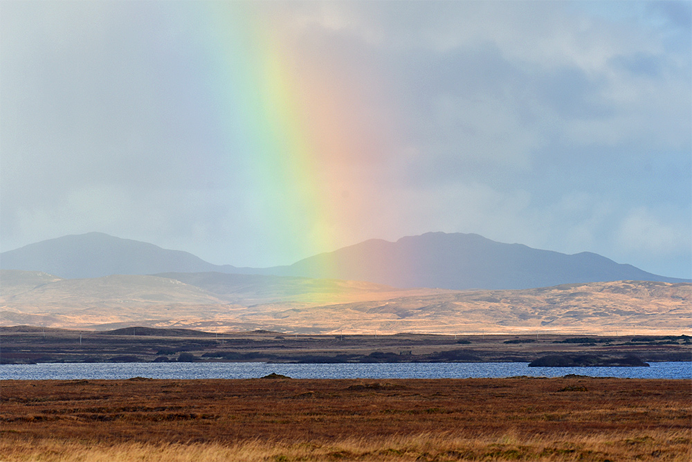 Picture of a rainbow behind a freshwater loch (lake)