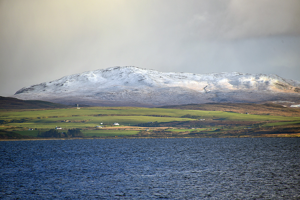 Picture of a snow capped hill on an island seen across a sea loch