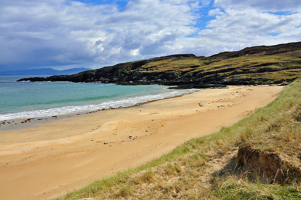Picture of the end of a beach, going over into a rocky headland