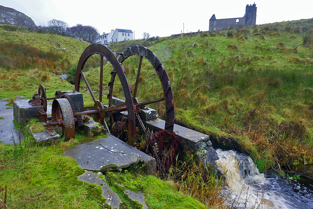 Picture of the remains of an old water wheel, a church ruin and some cottages in the background