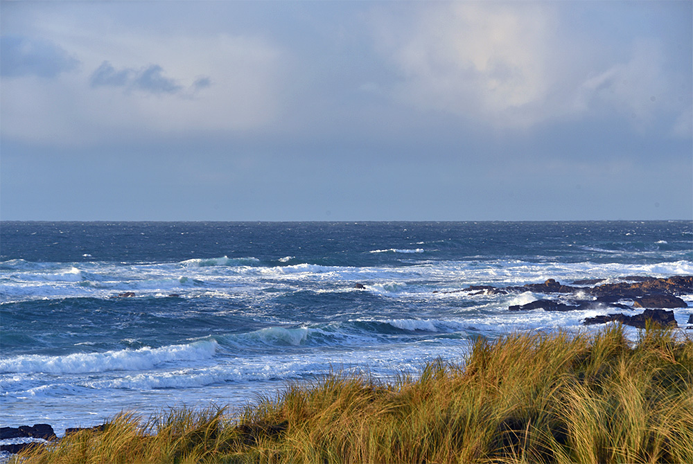 Picture of waves rolling in behind dunes in a bay