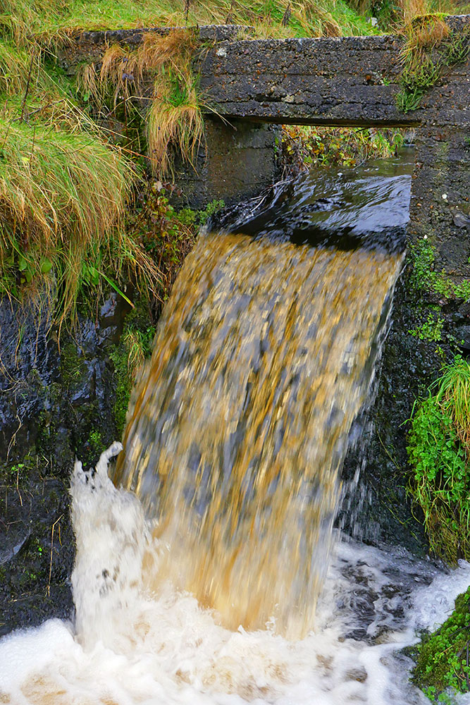 Picture of a mill stream flowing through a small weir gate