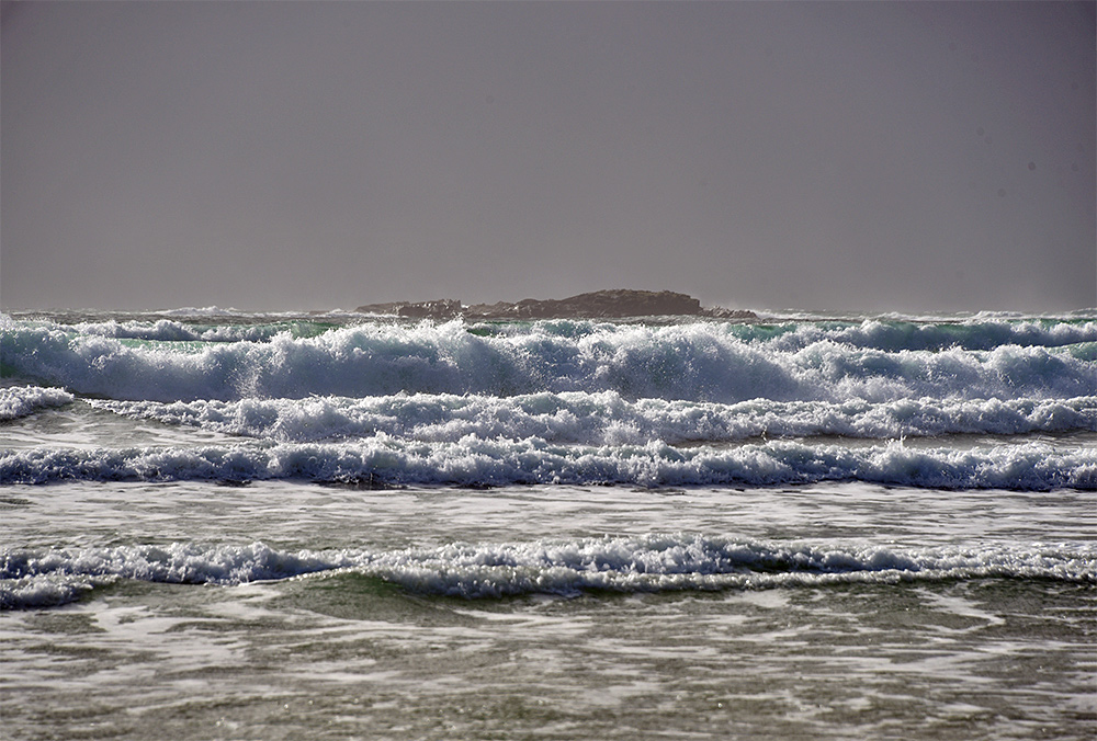 Picture of waves rolling on to a beach, a small rocky island in the background