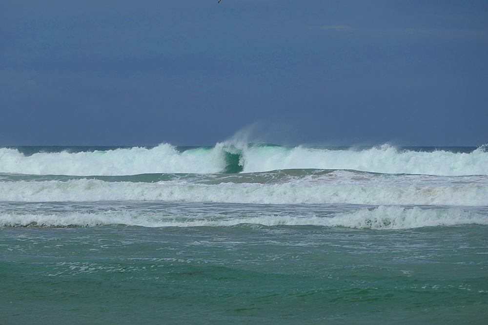 Picture of waves breaking as they reach a beach, a gap in the break in the centre of the picture