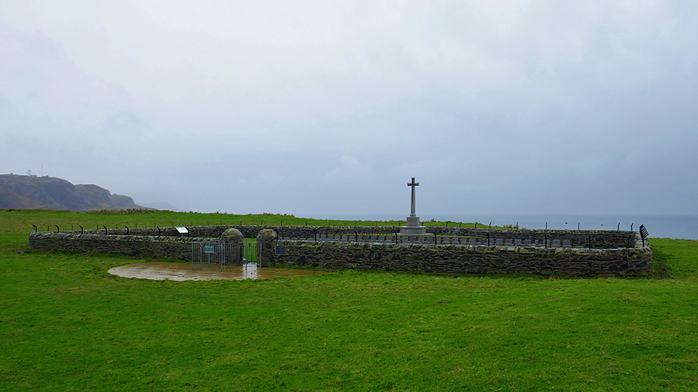 Picture of a small military cemetery in a field on a rainy day