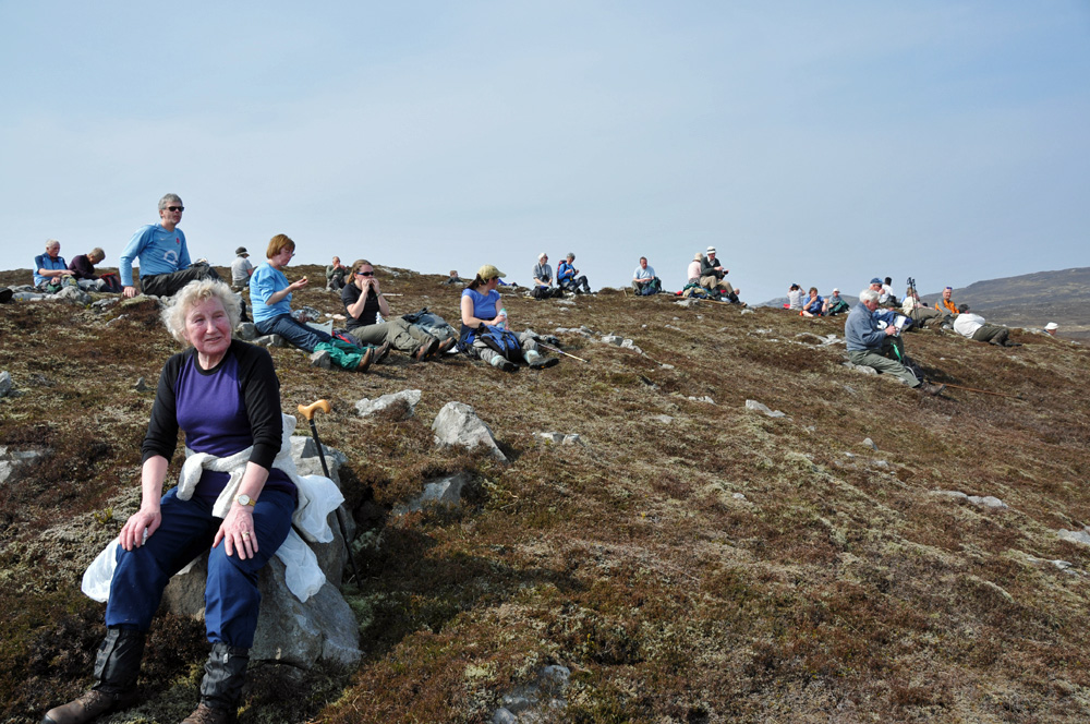 Picture of a large group of walkers taking their lunch break on a hill side