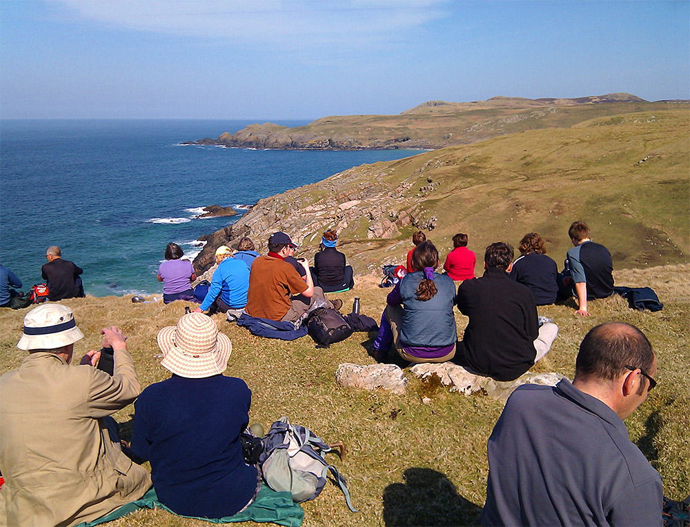 Picture of a group of walkers sitting on cliffs high above the sea during a coastal walk on a sunny day