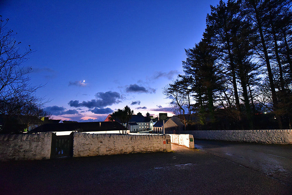 Picture of the entrance of Laphroaig distillery on Islay on a mostly clear evening with just some clouds on the horizon