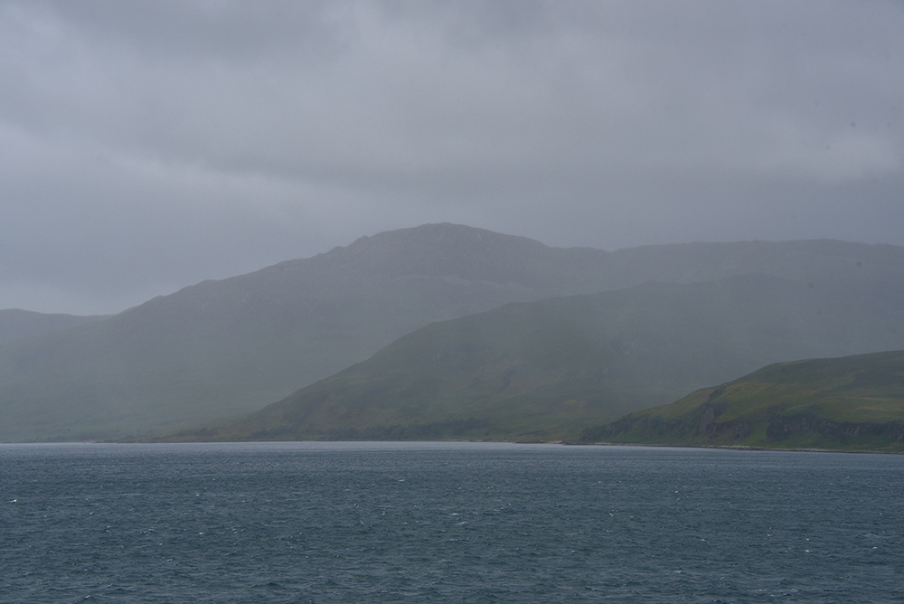 Picture of a row of hills along a sound between two islands on a rainy day