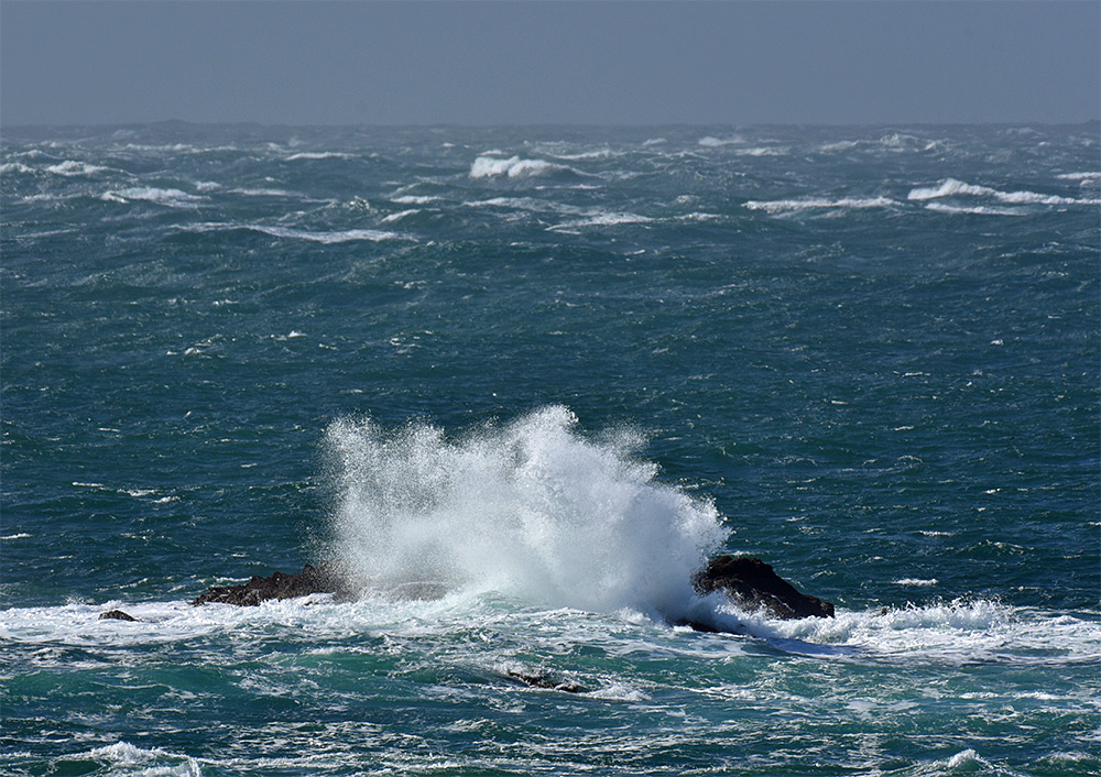 Picture of a wave breaking over rocks with a big splash