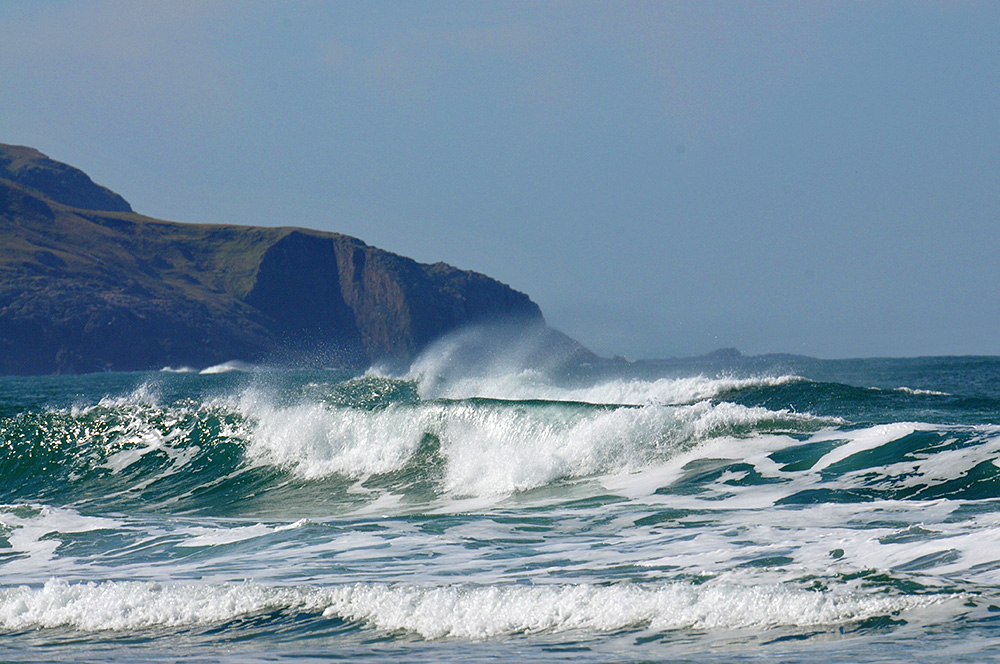 Picture of breaking waves with spray flying above them in a wide bay