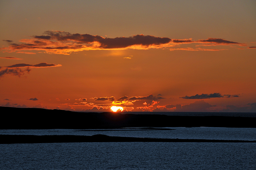 Picture of a colourful sunset seen across a freshwater loch (lake) with the ocean in the background