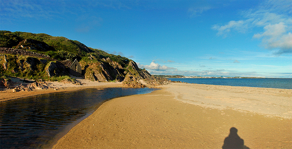 Picture of the end of a sandy beach with a village visible across a bay