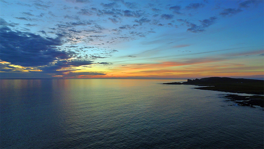 Picture of the sea off a coast in the gloaming, seen from a drone