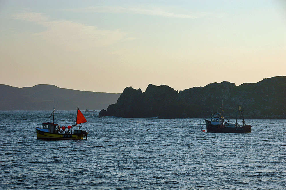 Picture of two fishing boats moored in a bay in the evening light