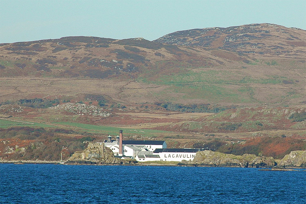 Picture of a castle ruin and a distillery on a coast, seen from a passing ferry