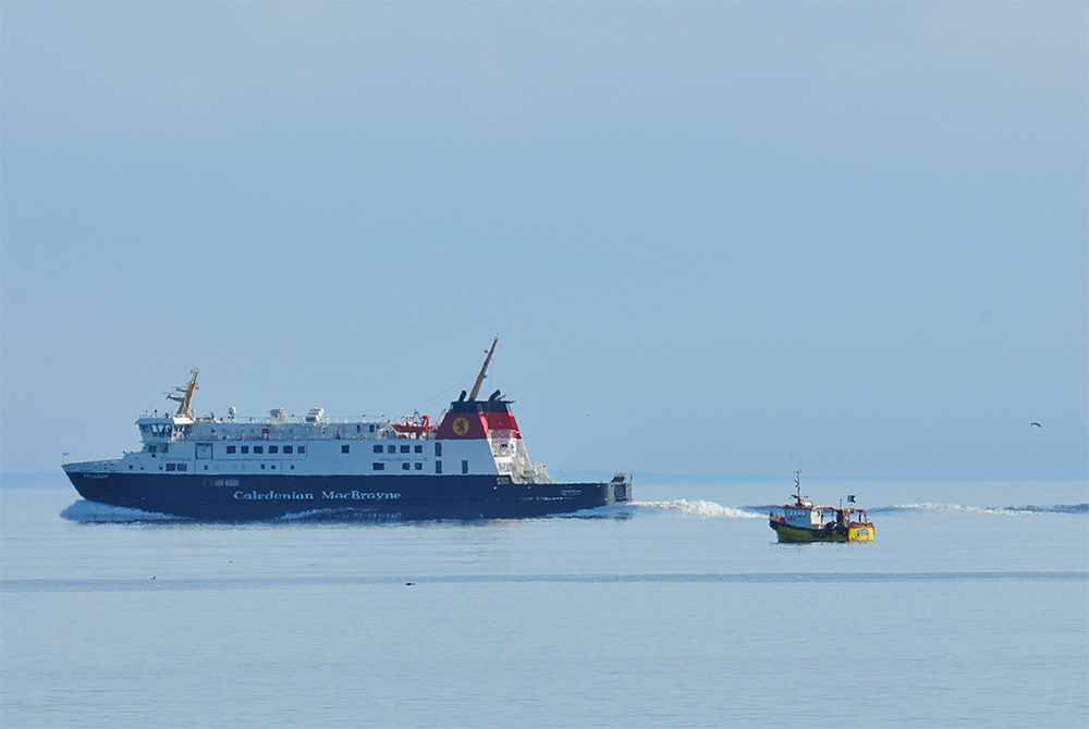 Picture of a Calmac ferry cruising past a small fishing boat in very calm seas
