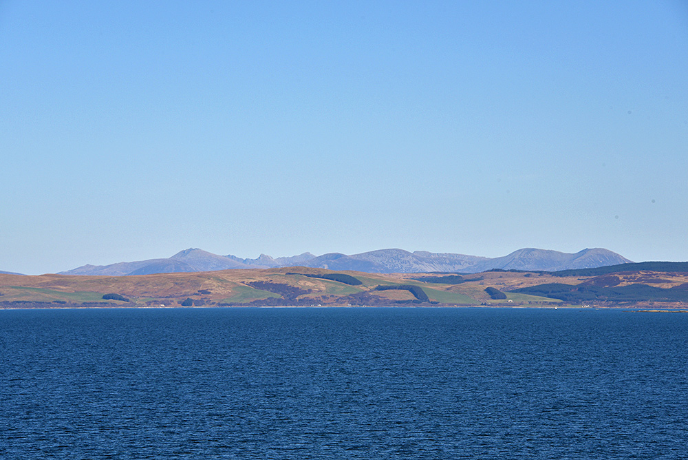 Picture of a view from a ferry across the sea to the mainland, the hills of an island visible behind it