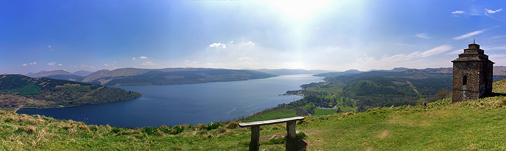 Panoramic picture of a view over a sea loch from a hill, an inviting bench in the foreground