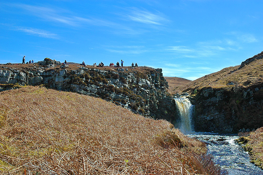 Picture of a group of walkers taking their lunch break on a hill just above a waterfall