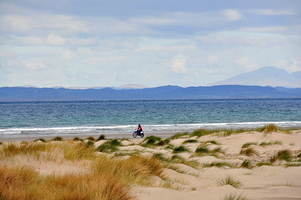 Picture of a motorbike driving along a beach behind dunes, other islands visible in the distance