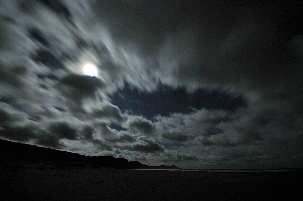 Picture of clouds moving over a bay with a beach on a partially cloudy full Moon night
