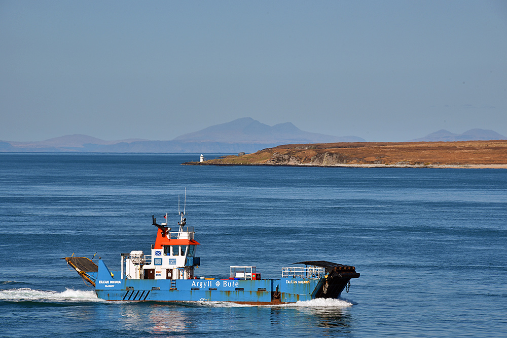Picture of a small car ferry in a Sound between two islands on a clear sunny day