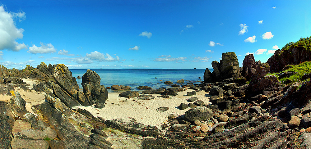 Panoramic picture of a beach with various rock formation and stones