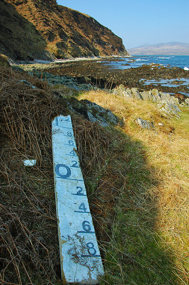 Picture of a broken water level board washed up on a remote shore