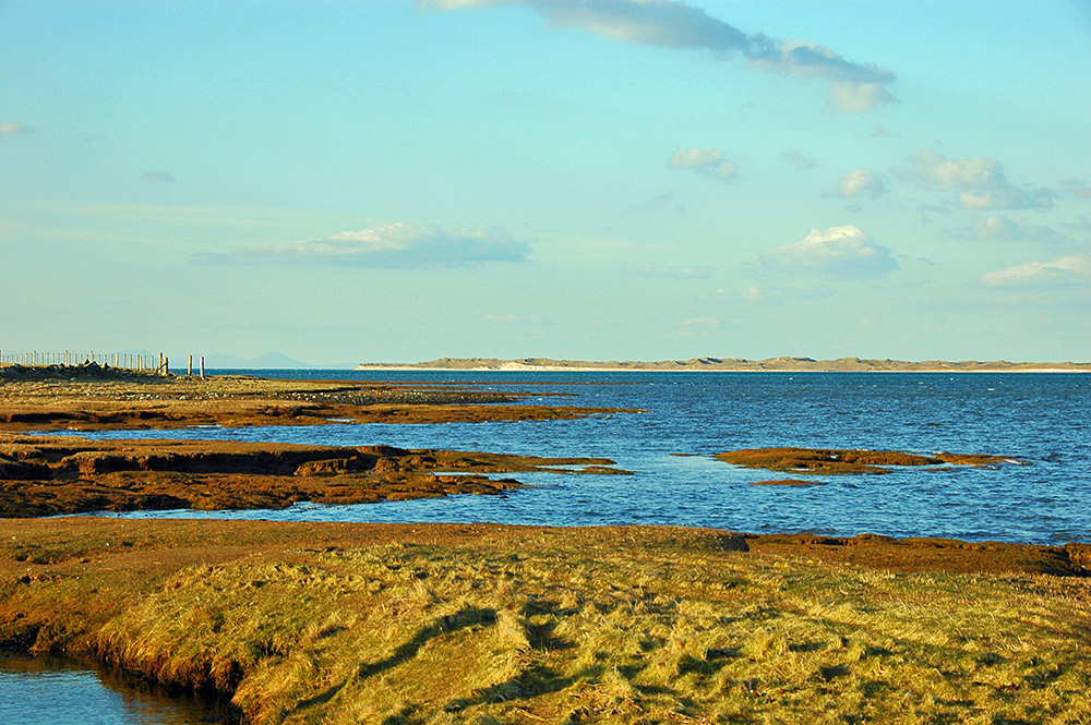 Picture of a view across a sea loch on an April evening, looking towards some dunes