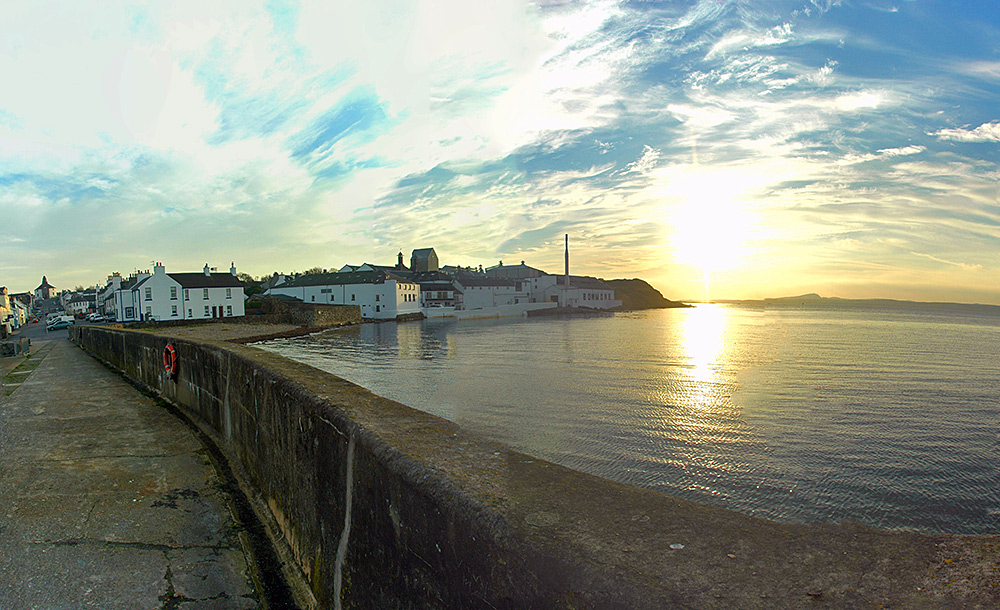 Panoramic picture of an approaching sunset seen from a pier, a distillery on the shore