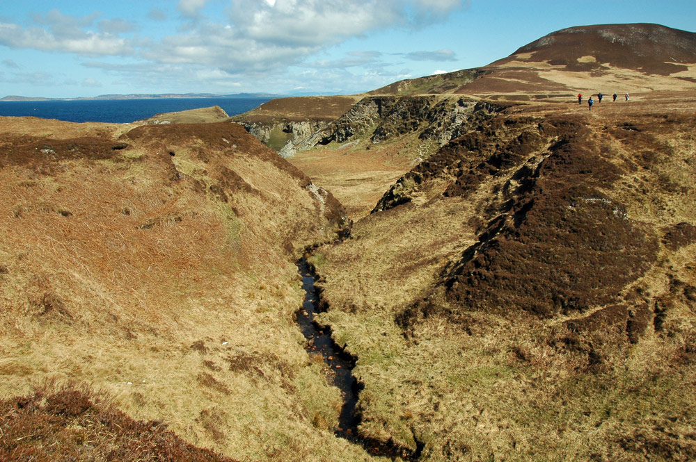 Picture of a burn (stream) flowing through a deep gully in a coastal landscape