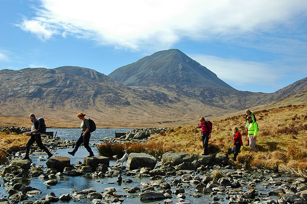 Picture of walkers crossing a small river using stepping stones, mountains in the background