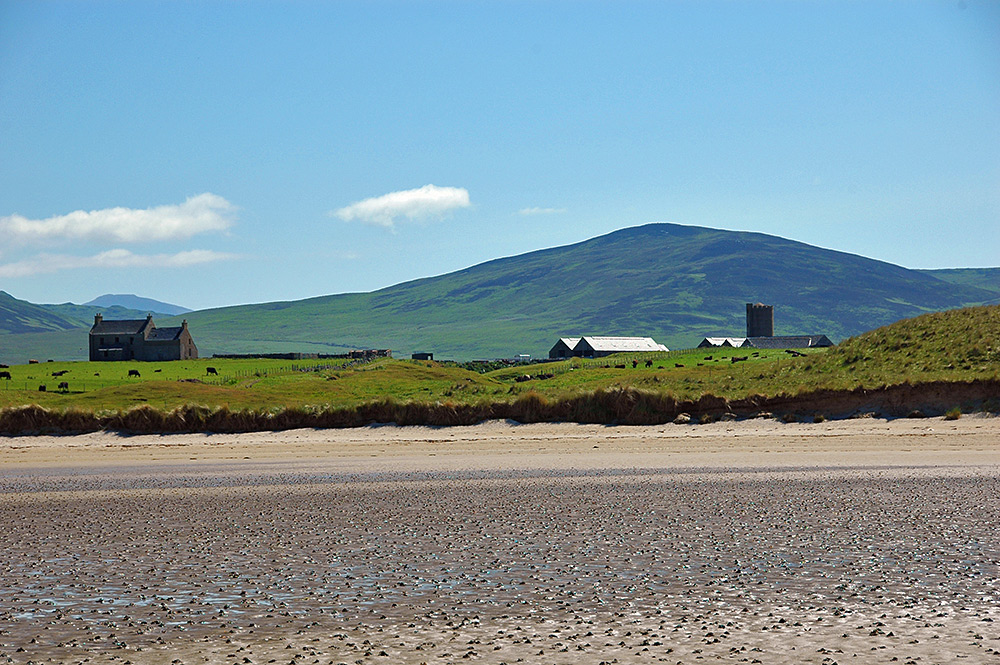 Picture of an old farm and farmhouse, seen from a beach