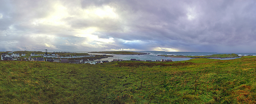 Panoramic picture of a small coastal village, protected by two small islands