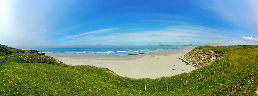 Panoramic picture of a view over a beach and some dunes from the top of the dunes