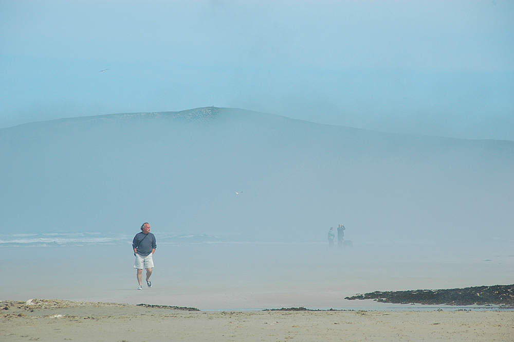 Picture of a few people walking on a beach with some low mist/fog around