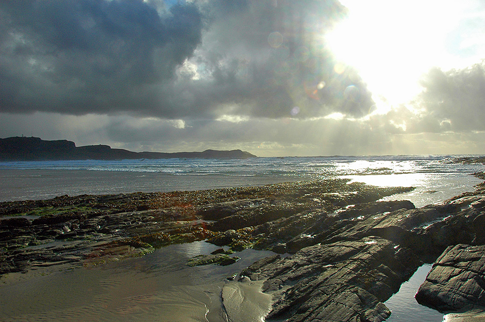 Picture of the sun breaking through showery clouds, illuminating rocks on a beach