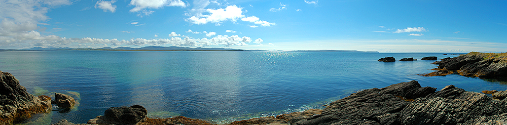 Panoramic picture of a large sea loch on an island on a sunny day