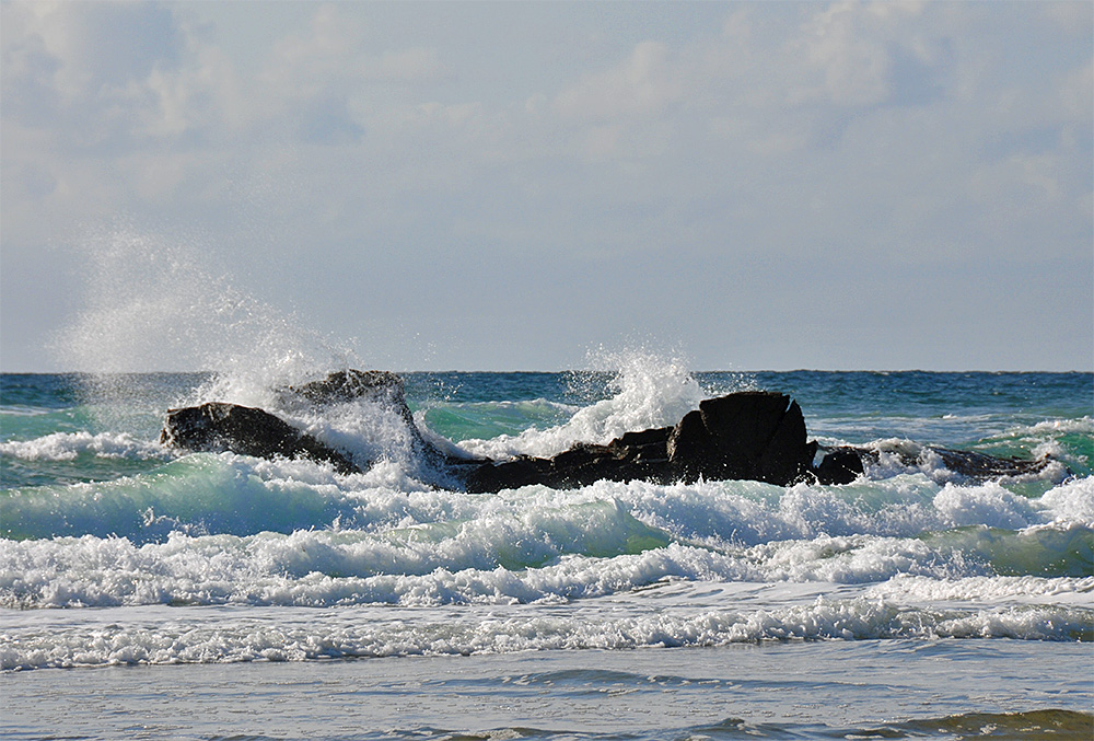 Picture of waves breaking over rocks at a beach