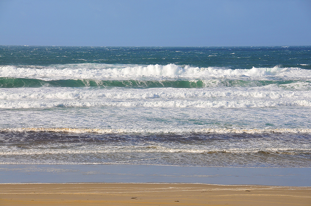 Picture of waves rolling on to a beach on a breezy day with sunny intervals
